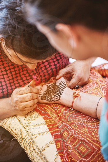 The henna tattoo artist (Mehndi) painting the hand of the women who was the guest in the indian wedding ceremony photo
