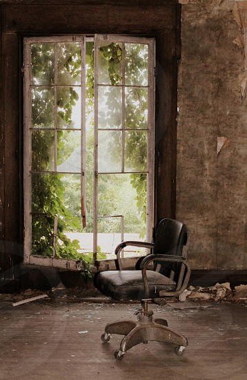 rolling chair in abandoned room with broken windows photo