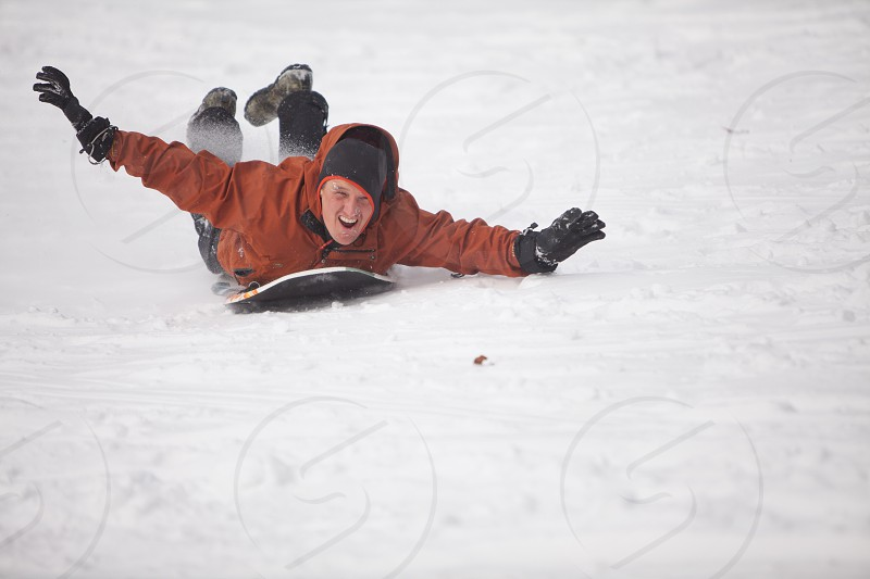 Father sledding down backyard hill during snowfall photo