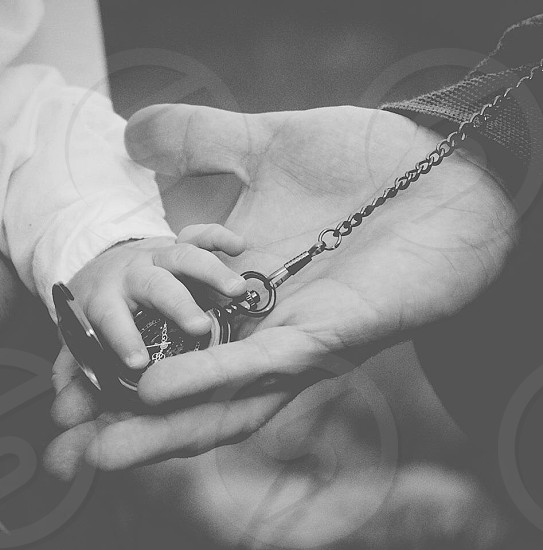 child touching metal pocket watch on person's hand photo