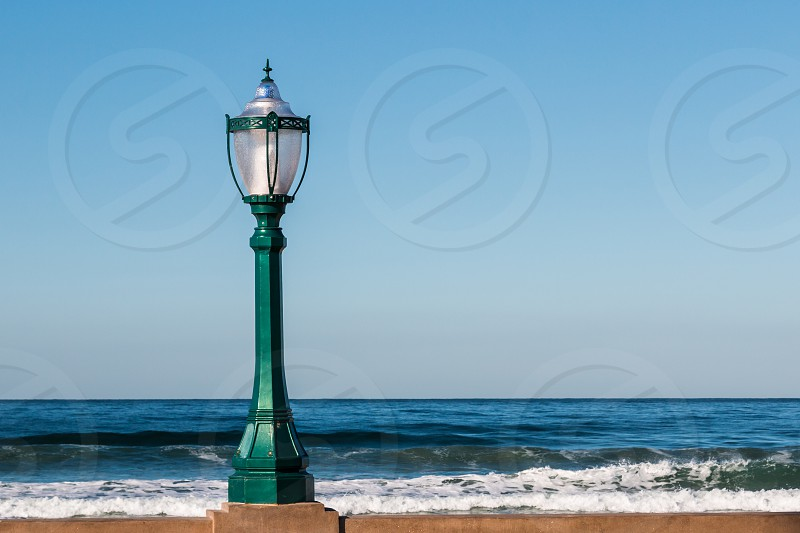 Lamp post on wall with ocean waves in the background.  photo