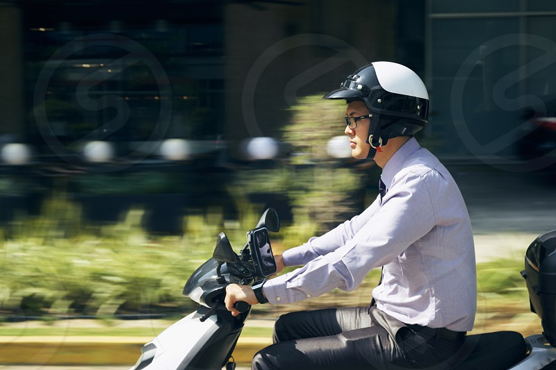 commuter business businessman motorcycle riding road scooter 30s adult asian blur blurred motion businesspeople chinese city commuting concentration driver driving entrepreneur fast going helmet male man mode of transport morning motion motion blurred moto office outdoors Panama people person speed street suit traffic transport transportation urban vehicle work workplace white photo