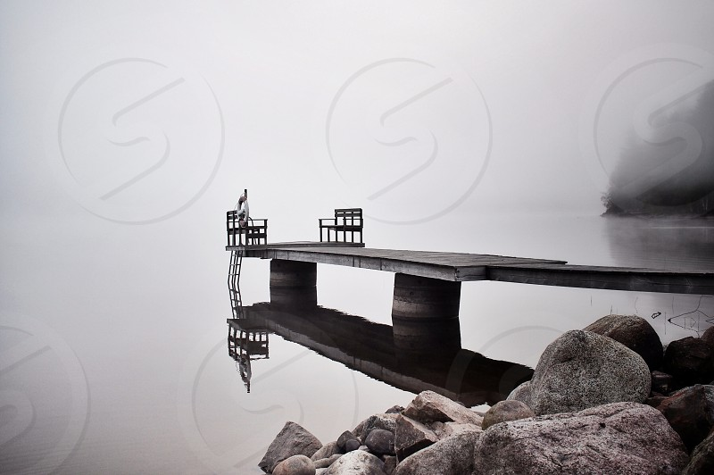 Reflecting reflections pier wooden fall autumn lake water calm mist fog foggy  photo