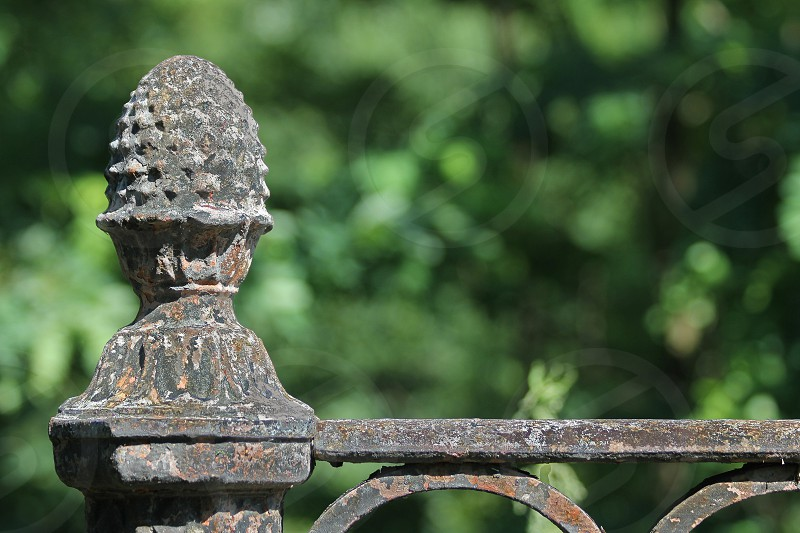 Old  Cast Iron Knob and Fence Against a Green Background photo