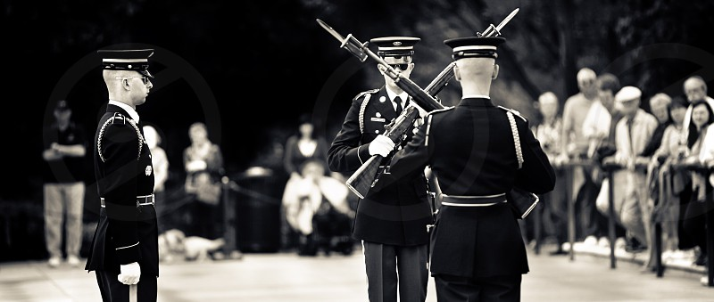 Three marines adjusting rifles and changing guards during a ceremony at the Tomb of the Unknown Soldier. photo
