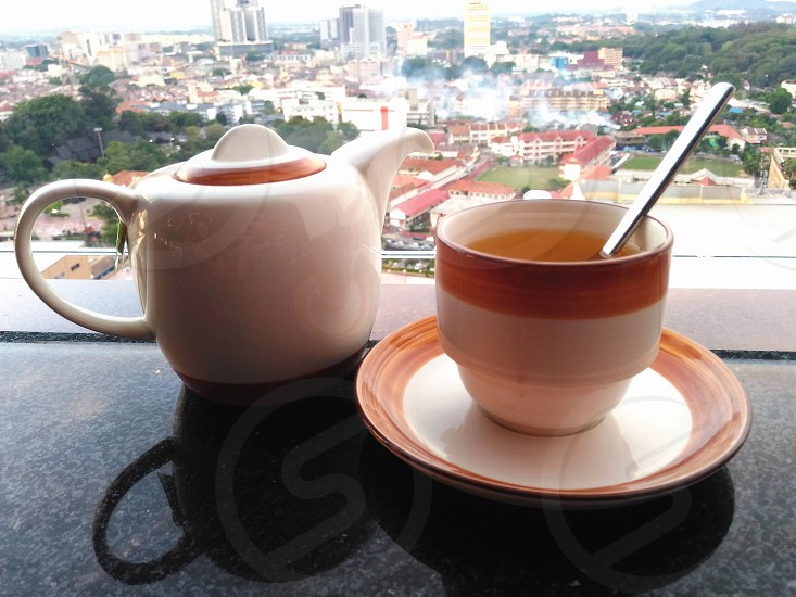 white and brown ceramic cup with silver utensil on brown and white ceramic round plate beside white ceramic kettle on marble platform viewing city during day time photo