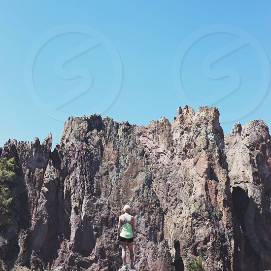 woman standing near gray rocky mountain photo
