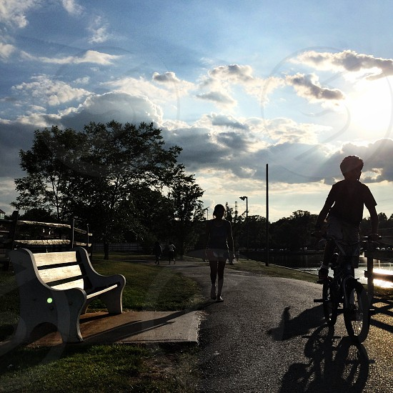on a sidewalk with a bench on the left side is a bicycling child followed by a person under blue sky with cumulus clouds during daytime photo