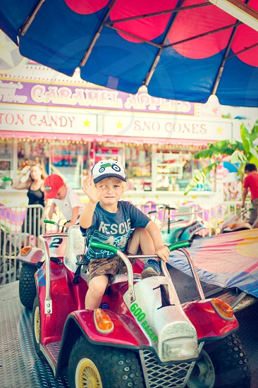 boy youth child amusement park ride fun summer fair yellow around circle carousel green blue hat cap happy rides blonde teeth smile carnival festival 4-wheeler four wheeler tractor ATV photo