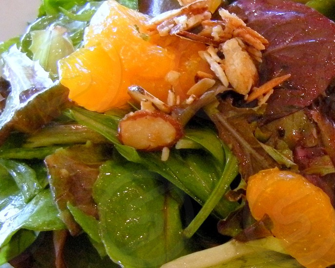 Salad with fresh local greens almonds and oranges photo