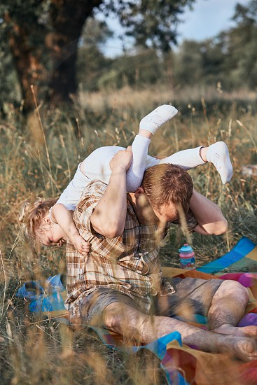 Father playing with little girl on a meadow close to nature. Parents and children sitting and playing on a blanket on grass. Candid people real moments authentic situations photo