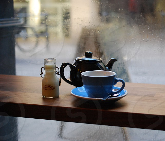 Teapot blue teapot and milk bottle on cafe counter in window. photo
