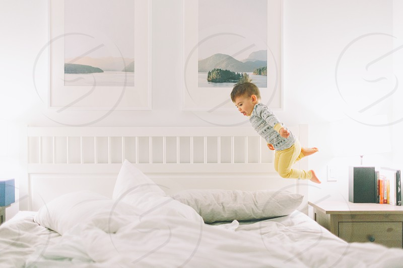 A little boy leaping from the nightstand on to the bed in his pyjamas. photo