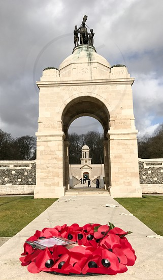 Outdoor day vertical portrait colour Delville Wood Somme France Europe European Battle Western Front World War One WWI WW1 First World War battleground war warfare trench Trenches memorial remembrance commemoration stone carved Canada Canadian mourning monument sky clouds blue poppy poppies wreath photo