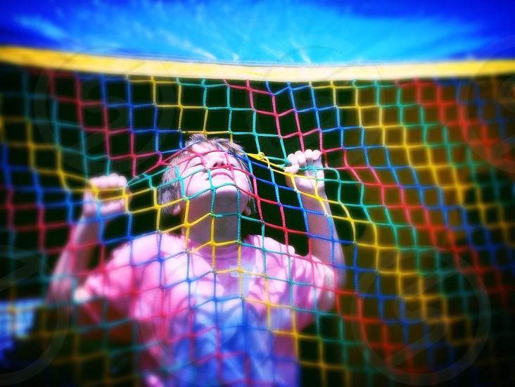 boy in pink shirt standing holding a net photo