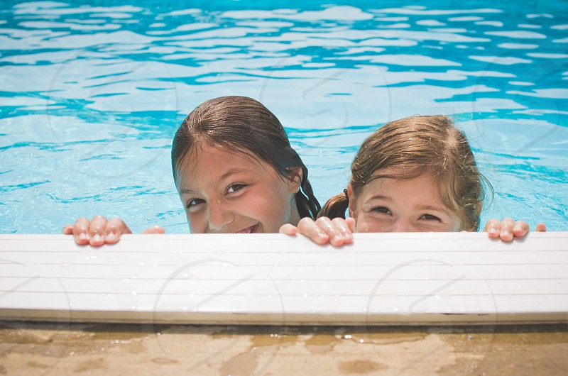 Two girls peeking over the side of a pool smiling. photo