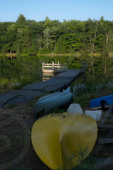 Lake dock in summer green trees overturned canoes photo
