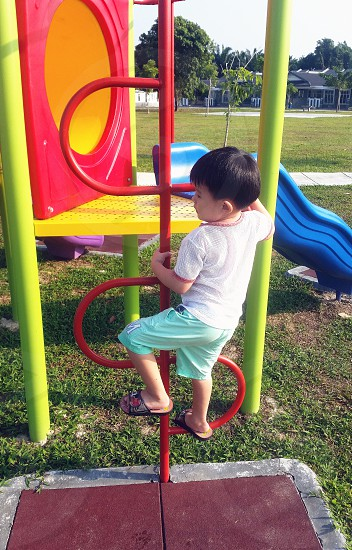 boy in white shirt playing on the playground photo