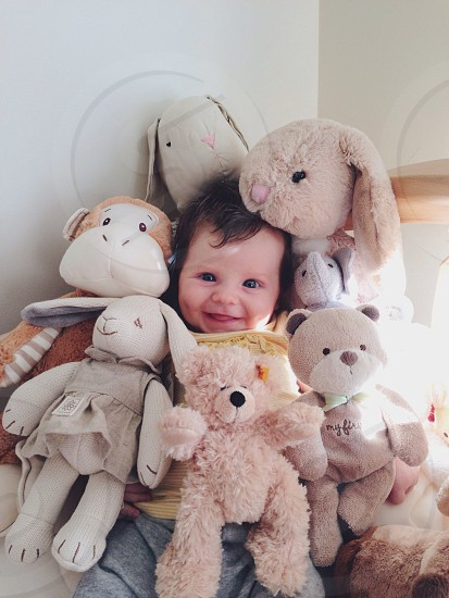 baby beside brown and white monkey plush toy photo
