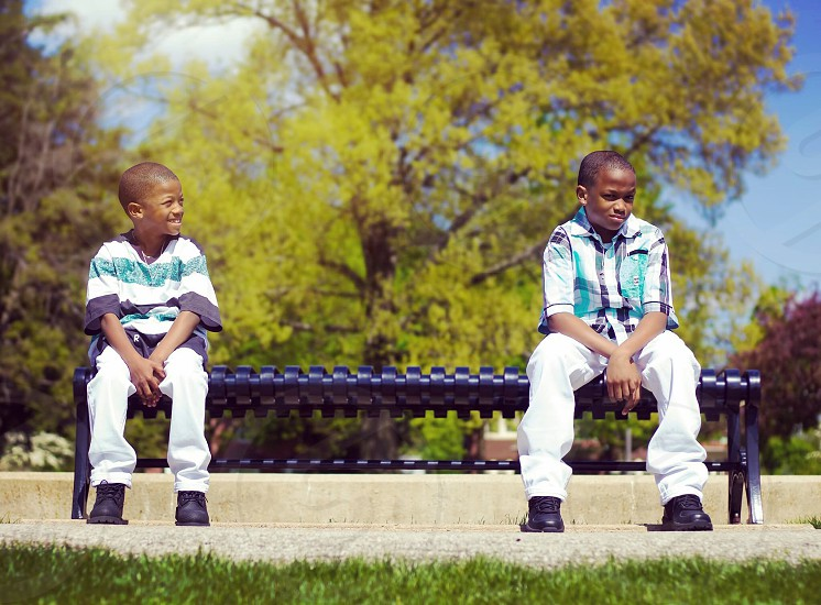 two boy wearing same colored shirts and pants sitting on opposite sides of blue bench near trees at daytime photo