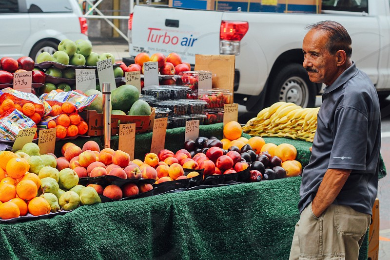 man standing in front of a fruit stand with orange apple and banana fruits near the road photo