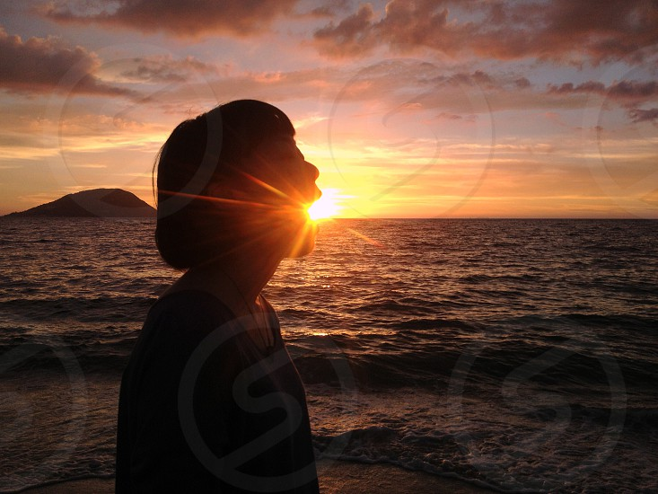 woman standing on seashore with sun on mouth photo