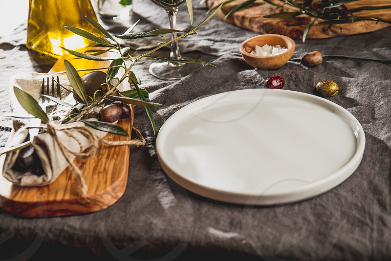 Table setting with gray Linen tablecloth and napkin white plate cutlery and and olive tree branch boards decoration. Close up. photo