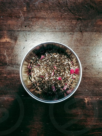 red flower petals and seed in stainless steel bowl above wooden desk photo