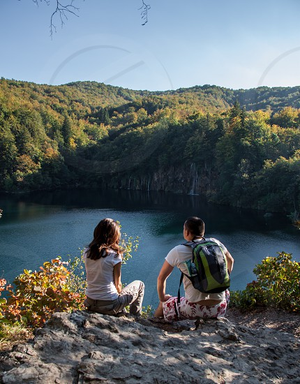 people looking at lake and mountains photo