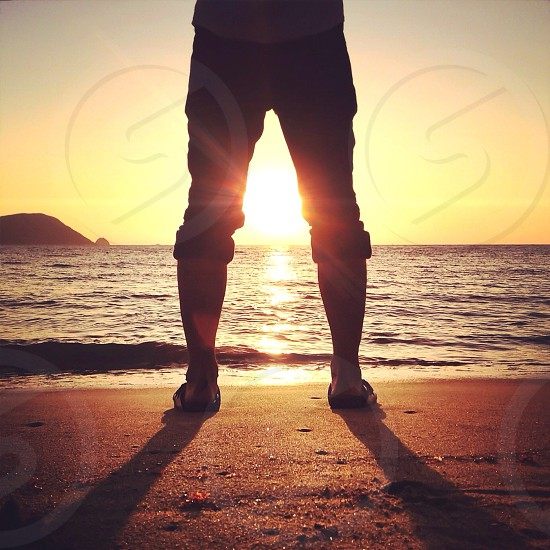 sunset between man's legs standing at the beach photo