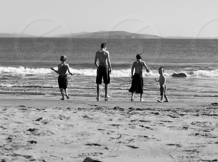 4 boy standing on seaside photo