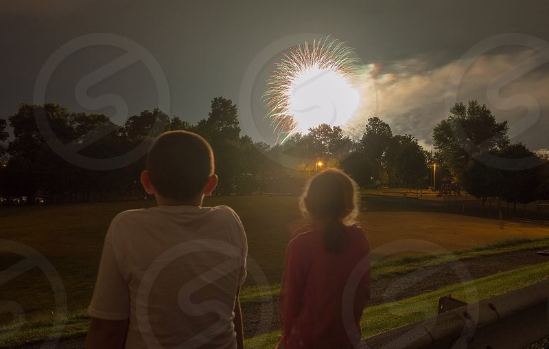 boy and girl watching fireworks display photo