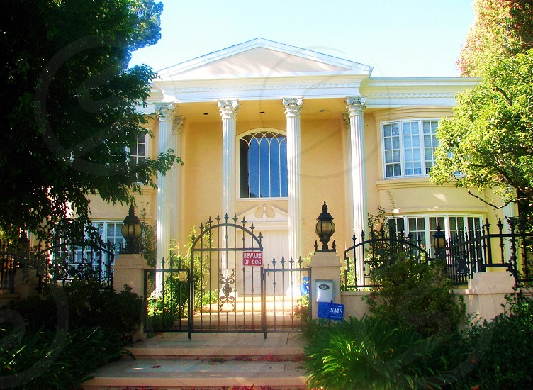 white mansion house with black steel gate photo