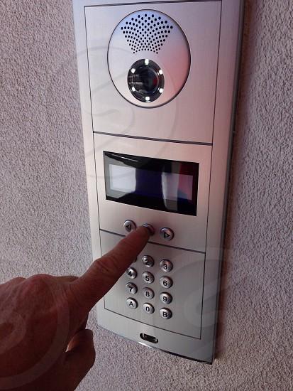 POV finger doorbell intercoms entry. Apartment  photo