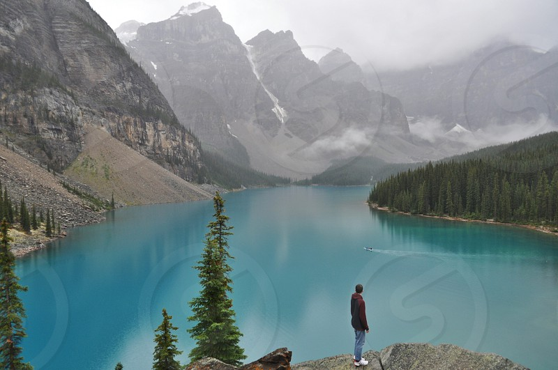 a man watches over a lake in the rocky mountains in Alberta Canada photo