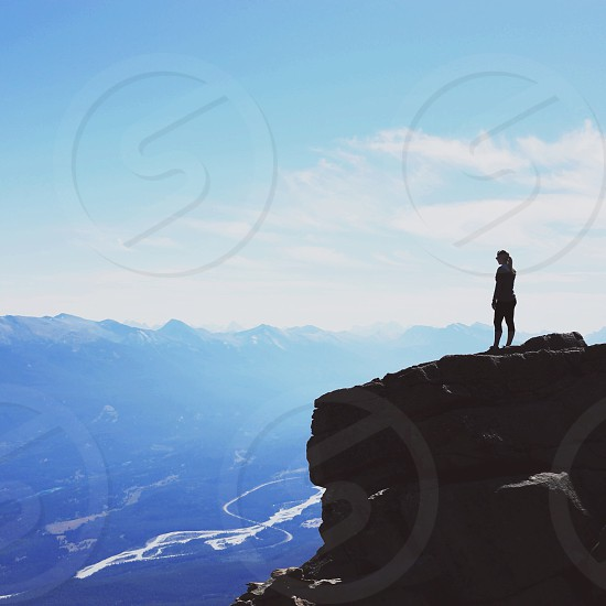 silhouette of person standing on black rocky mountain photo