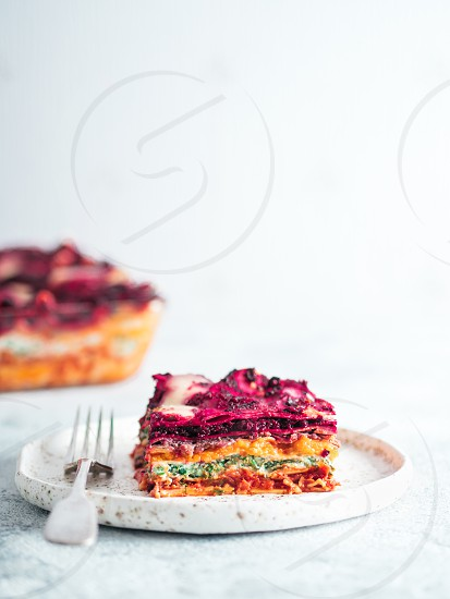 Vegetable Packed Rainbow Lasagne on craft plate.Ideas and recipes for healthy vegetarian dinner or lunch. Lasagne with beetrootpumpkinmushroomsricottaspinachmozarella on white table. Copy space photo