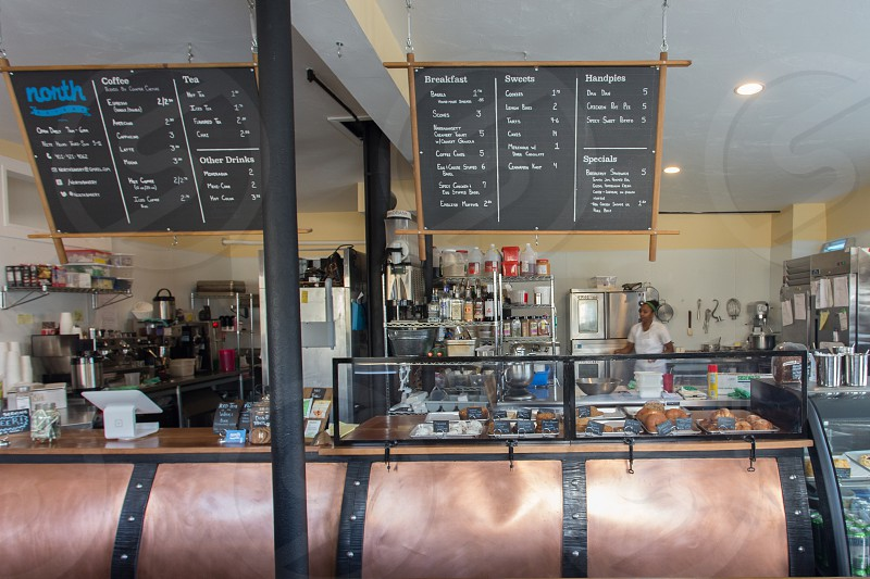 black and brown chalk board menu over food display cabinet inside restaurant photo