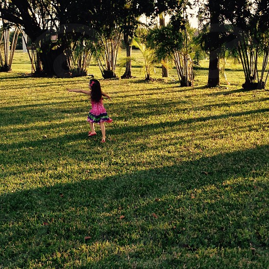 Childhood running kid girl trees grass field shadows photo