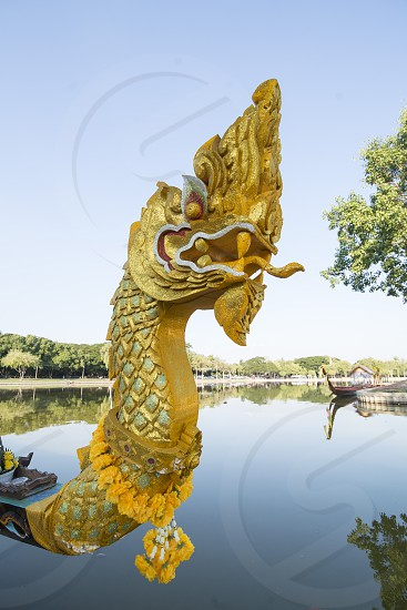 a dragon longboat at the lake at the Historical Park in Sukhothai in the Provinz Sukhothai in Thailand.   Thailand Sukhothai November 2018 photo