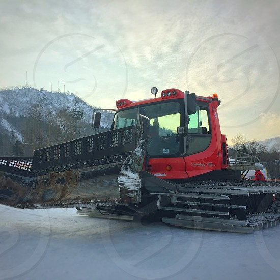 closeup photography of a red and black front loader under white clouds during daytime photo