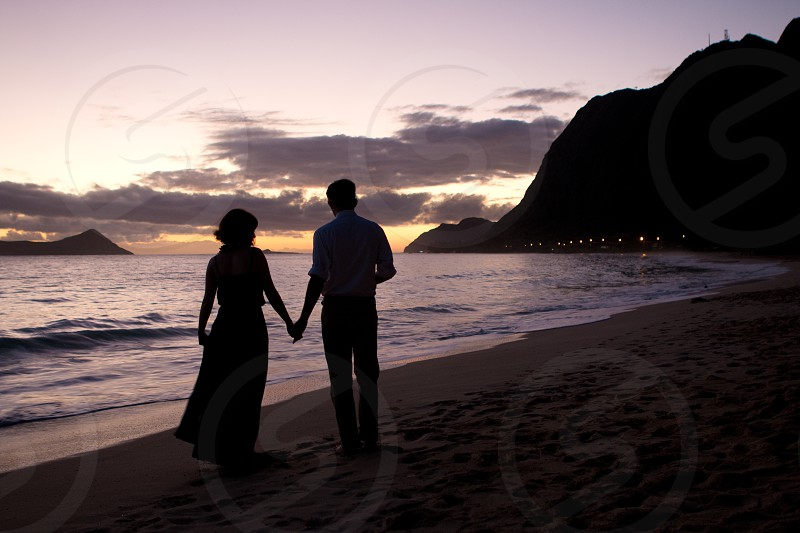 man and woman standing on sea shore holding hands under cloudy sky during sunset photo