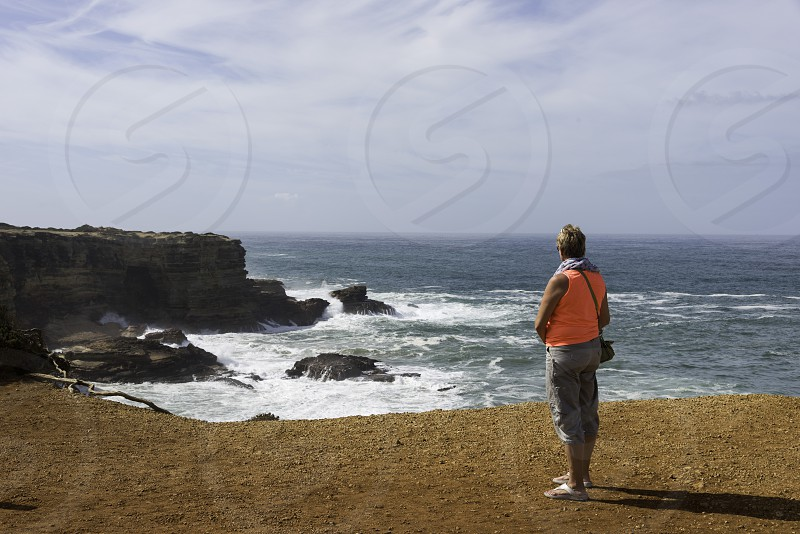 adult blond woman in orange shirt looking at the waves at the portugal coastline in Alentejo photo