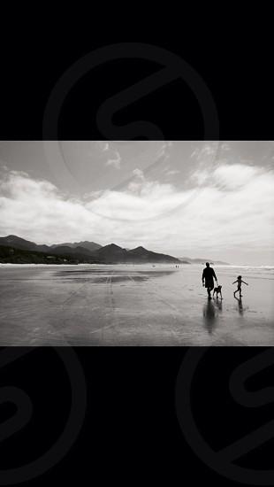 grayscale photography of man woman and dog walking on seashore near mountain photo