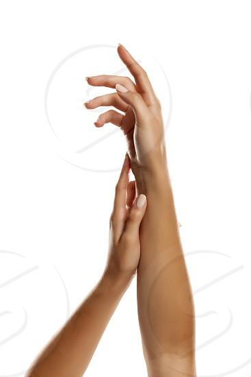 closeup of female hands applying hand cream on white background photo