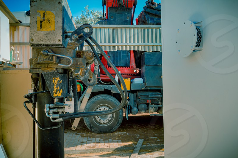 Closeup of hydraulic pistons of a parking rigging truck with heavy lifting crane arm machine. It is parked near a residential or industrial area with an emergency bomb shelter in Sderot Israel. photo