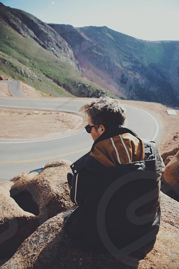 Young man sitting on rocks staring at curvy road photo