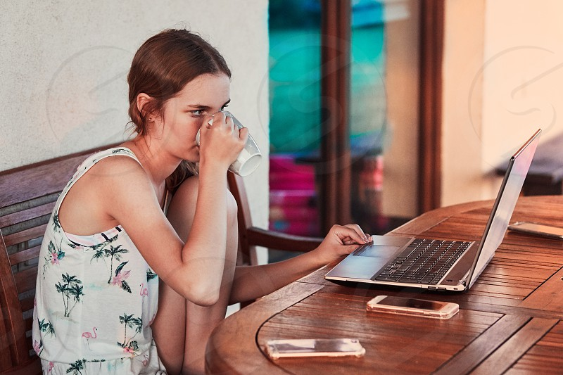 Woman working at home using portable computer sitting on patio on summer day photo