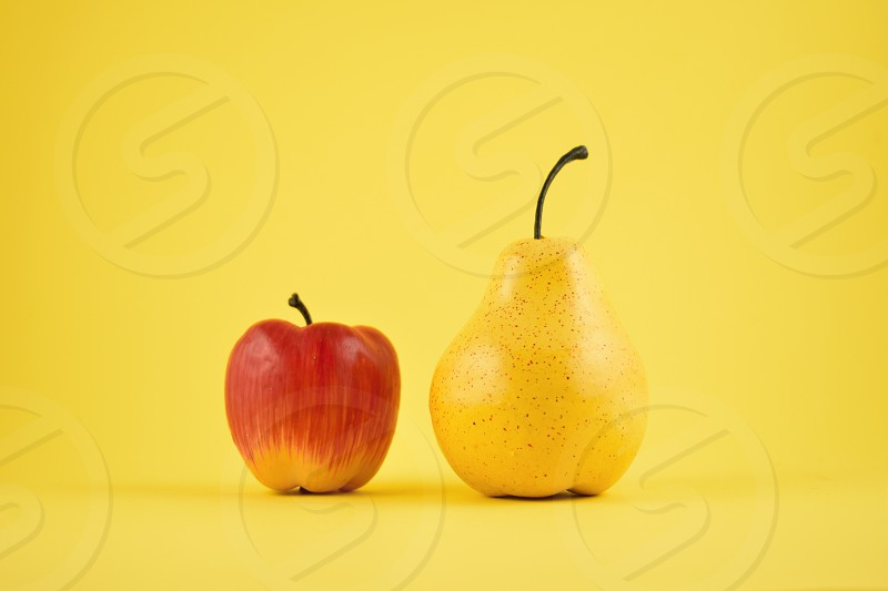 Pear and apple decoration. Yellow pear and red apple on a yellow background. Fruit home decor. Plastic decorative fruit photo