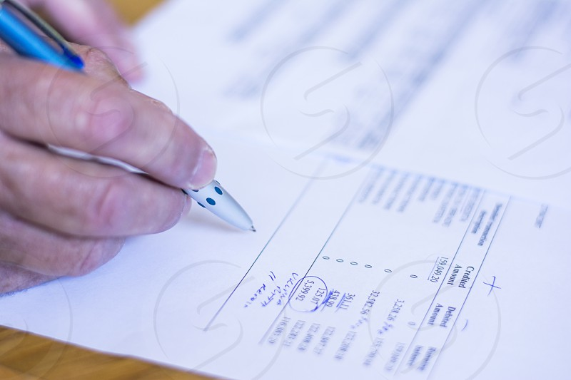Man hand signing bank papers for credit. photo
